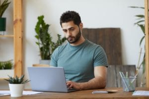 Bearded Man using laptop at Home Office