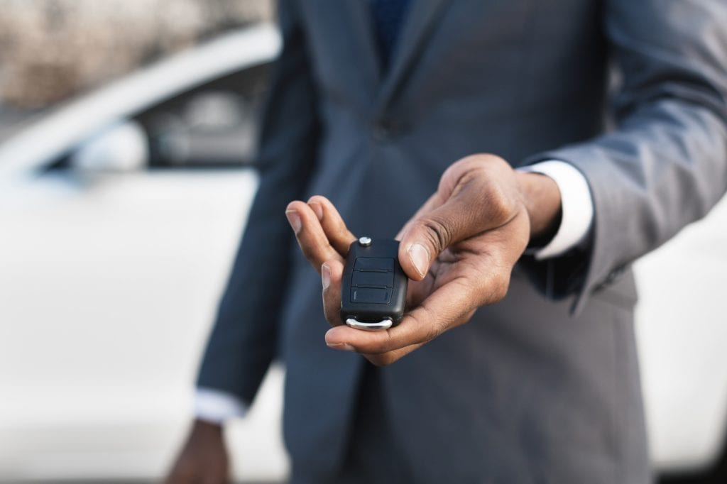 Car sale concept. Man hand giving car key