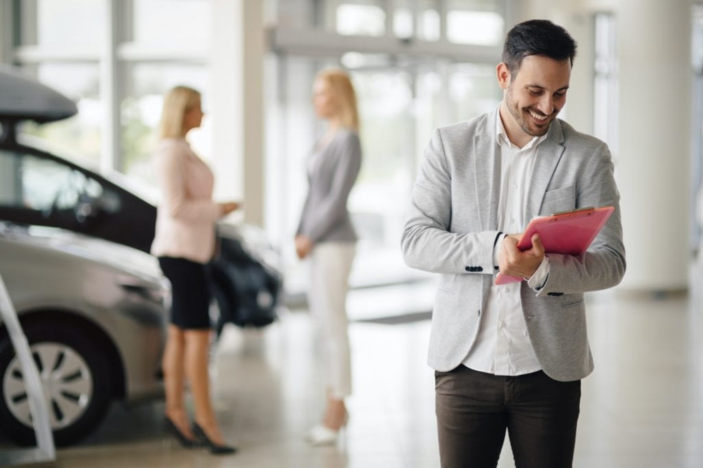 Salesperson selling cars at dealership