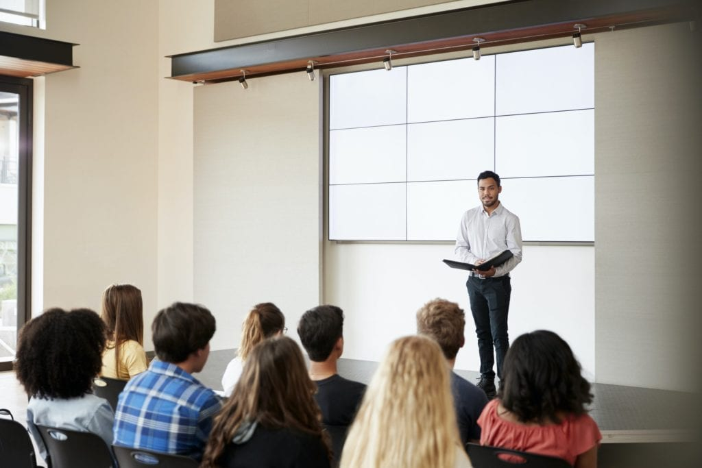 Teacher Giving Presentation To High School Class In Front Of Screen