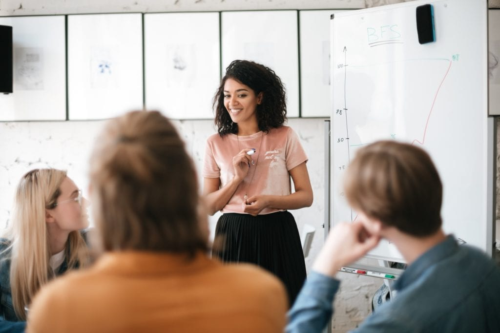Young beautiful business woman giving presentation to coworkers